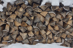 Stack of firewood under snow. birch firewood. close up Royalty Free Stock Image