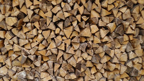 Stack of firewood. Wooden wall, background Stock Photo