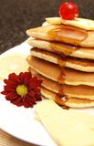 Stack of flapjacks with syrup. Stack of flapjacks with a red flower. A cherry is lying on top of the stack of flapjacks stock images