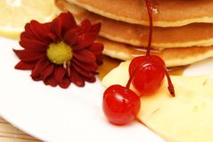 Stack of flapjacks with syrup. Stack of flapjacks with a red flower. Two cherries is lying next to the stack of flapjacks royalty free stock photos