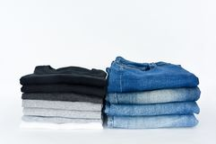 Stack of folded black, grey and white color monochrome t-shirt and indigo blue jeans on white background royalty free stock photos