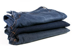 Stack of folded blue jeans on a white background Stock Photo