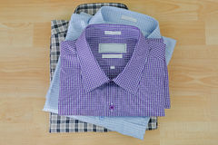 Stack of folded checked clothes, three 3 shirts after ironed ready to pack. On wooden background royalty free stock photography