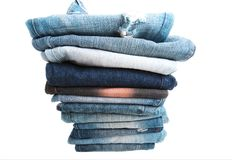 Stack of folded clothes, blue jeans pants, dark blue denim trousers on white background Royalty Free Stock Photo