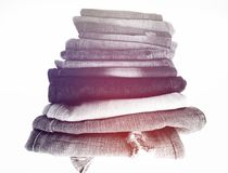 Stack of folded clothes, blue jeans pants, dark blue denim trousers on white background Royalty Free Stock Image
