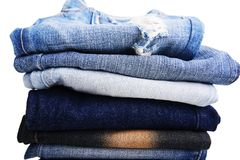 Stack of folded clothes, blue jeans pants, dark blue denim trousers on white background Stock Image
