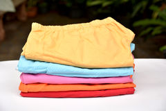 A stack of folded clothes on a white table on nature. stock photo