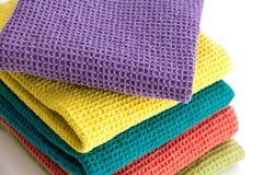 Stack of folded colorful kitchen towels, on white. Closeup background Stock Photos