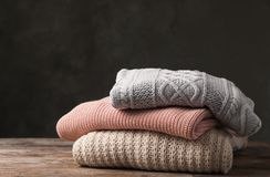 Stack of folded knitted sweaters on table. Space for text royalty free stock photo