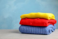 Stack of folded knitted sweaters on table. Space for text royalty free stock photography