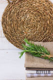 Stack of folded linen towels wicker rattan coaster on white wood background, twig of rosemary, kitchen interior. Concept stock photo