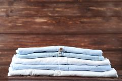 Folded shirts. Stack of folded shirts on brown wooden background royalty free stock images