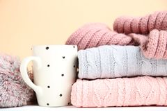 Folded sweaters with cup and scarf. Stack of folded sweaters with cup and scarf on beige background royalty free stock photo