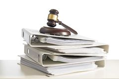Stack of folders and a judge gavel on a desk, isolated on a whit stock photos