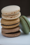 Stack of Four Assorted French Macarons on a Plate. A stack of four French macarons: chocolate, vanilla, caramel, and pistachio. Natural coloring and natural stock image