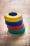 Stack of four rolls insulating tape on wooden Stock Photo