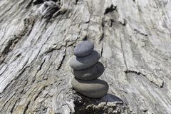 Stack of four smooth stones on a large driftwood log royalty free stock images