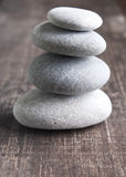A stack of four zen rocks. Close up of four zen rocks on old wooden plank Stock Image