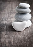 A stack of four zen rocks. Close up of four zen rocks on old wooden plank Stock Photo