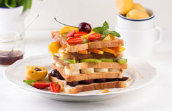 Stack of French toast with fresh strawberries, peaches, cherry, kiwi and banana Stock Photos