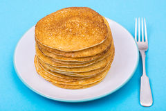 Stack of fresh delicious pancakes on white plate on blue backgro Royalty Free Stock Photos