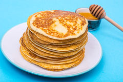 Stack of fresh delicious pancakes on white plate on blue backgro Stock Images