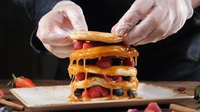 Stack of fresh fluffy pancakes decorated on top with forest berries. Putting pancake layer on top. Delicious, healthy. American breakfast. Fresh bakery concept stock video footage