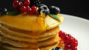 Stack of fresh fluffy pancakes decorated on top with forest berries rotating on plate and pouring honey syrup. Delicious stock video footage