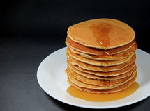 Stack of Fresh Homemade Pancakes with Maple Syrup, Served on White Plate. Black Background royalty free stock photos