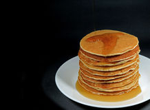 Stack of fresh homemade pancakes with maple syrup served on white plate, black background. With free space for text or design stock photo