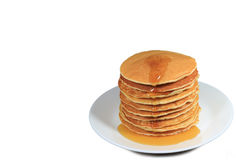 Stack of fresh made pancakes with maple syrup served on white plate, white background with free space for design Royalty Free Stock Images