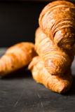Stack of freshly baked croissants on black background, golden delicious crust,close up,eye level view Royalty Free Stock Images