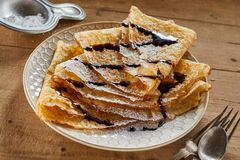 Stack of freshly made fried sugared Crepe. S drizzled with chocolate sauce and serves on a plate with a vintage sugar spoon or strainer on a wooden table royalty free stock photos