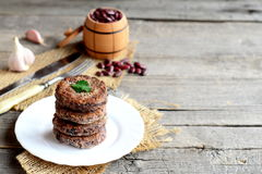 A stack of fried bean cutlets on a plate. Vegetarian cutlets cooked from red beans. Raw red beans in small barrel, garlic, fork Stock Image