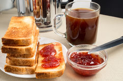 Stack of fried slices of bread and bowl of strawberry jam Stock Photos