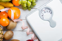 Stack of fruits, white weight scale and tailor meter. On wooden board. Concept of diet and healthy lifestyle stock image