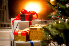 Stack of gift boxes under Christmas tree at fireplace Stock Photography