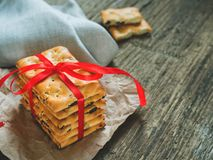 A stack of gift cookies wrapped with a red festive ribbon on a wooden background. Copy space royalty free stock photography