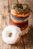Stack of glazed multicolored donuts close-up. vertical Stock Photos
