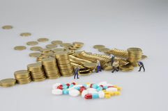 Stack of gold coin with miniature people and medicine Royalty Free Stock Image