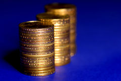 Stack of Gold Coins. Several stacks of gold coins on blue background Stock Photos