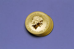 Stack of gold coins. Stack of australia gold coins shot in purple background Royalty Free Stock Images