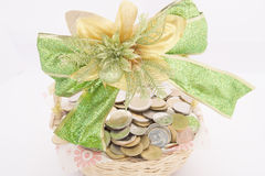 Stack of gold coins in basket with green ribbon Royalty Free Stock Photography