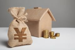 Stack of gold coins and the figure of crafting house. Bag with money and yuan sign. Investment in estate property. Home rental, stock photos