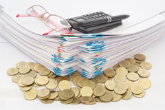 Stack of gold coins with pile of paperwork. Have pen with spectacles and calculator on a white background Stock Photography
