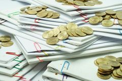 Stack of gold coins on pile of white scattered paperwork Stock Images