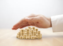 Stack of golden coins covered by hand Stock Images