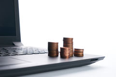 Stack of golden coins on laptop  on white Royalty Free Stock Photo
