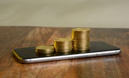 Stack of Golden Coins on Mobile Screen - Earning concept.  Stock Photography