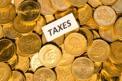 Taxes sign on golden coins Stock Photos